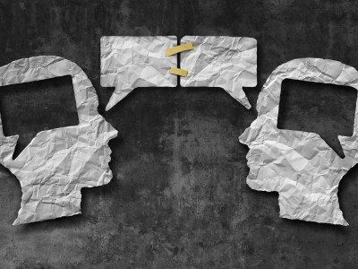 Speaking together media concept as two crumpled pieces of paper shaped as a human head with talk bubbles or speech bubble icons taped as a communication symbol for business understanding and compromise agreement.