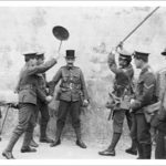 DCLI recruiting march, St Just in Penwith, Cornwall. 18th June 1915. The 3rd Duke of Cornwall's Light Infantry recruiting march on Friday 18th June 1915. Some soldiers are 'arresting' another who is wearing a top hat. Photographer: Arthur William Jordan.