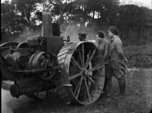 Two members of the Women's Land Army being shown an early tractor by a man in army uniform. Photographer: A W Jordan. © From the collection of the RIC (TRURI-1972-2-266).