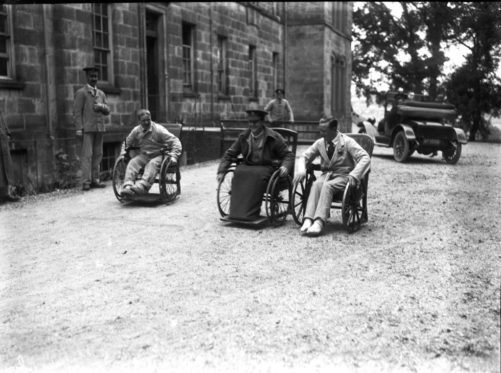 Three patients in wheelchairs, one in military uniform, engaged in a race outside the Royal Cornwall Infirmary, with hospital staff looking on, probably on July 21st 1916. Photographer: A W Jordan. © From the collection of the RIC.